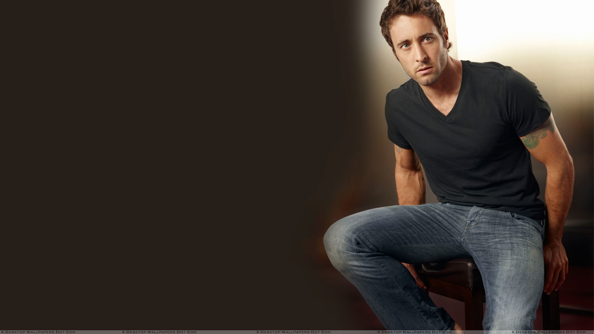 Alex o loughlin in black t shirt and blue jeans sitting Black shirt blue jeans