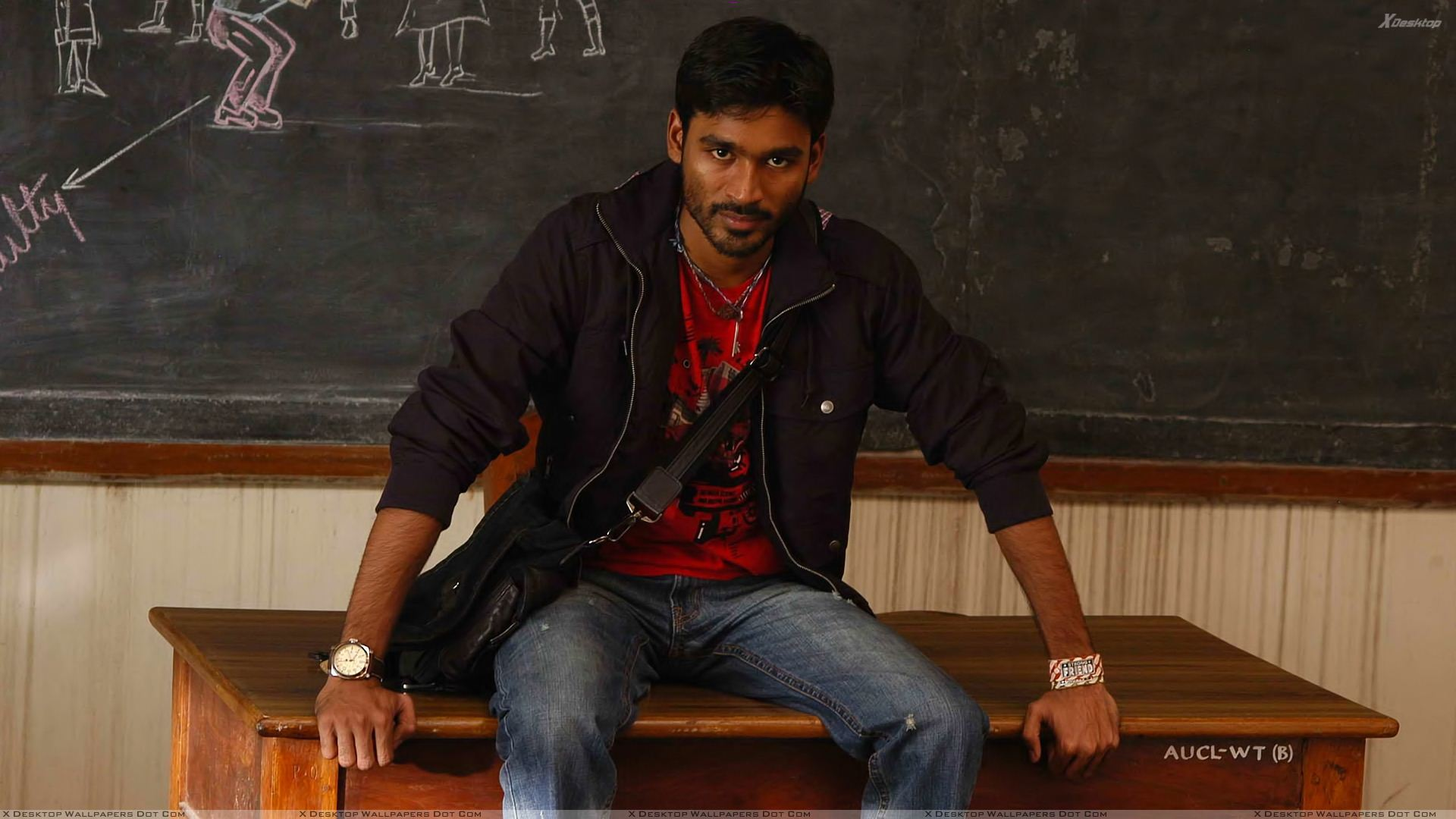 dhanush sitting pose on table in classroom in kutty movie wallpaper