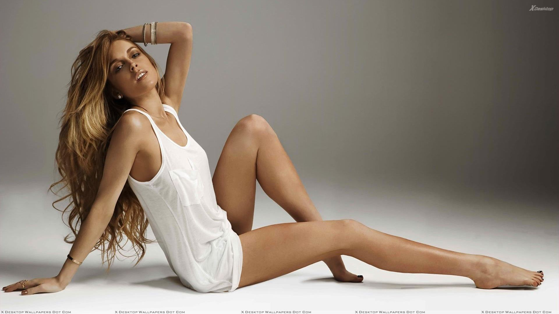 lindsay lohan sitting pose in white top looking at camera