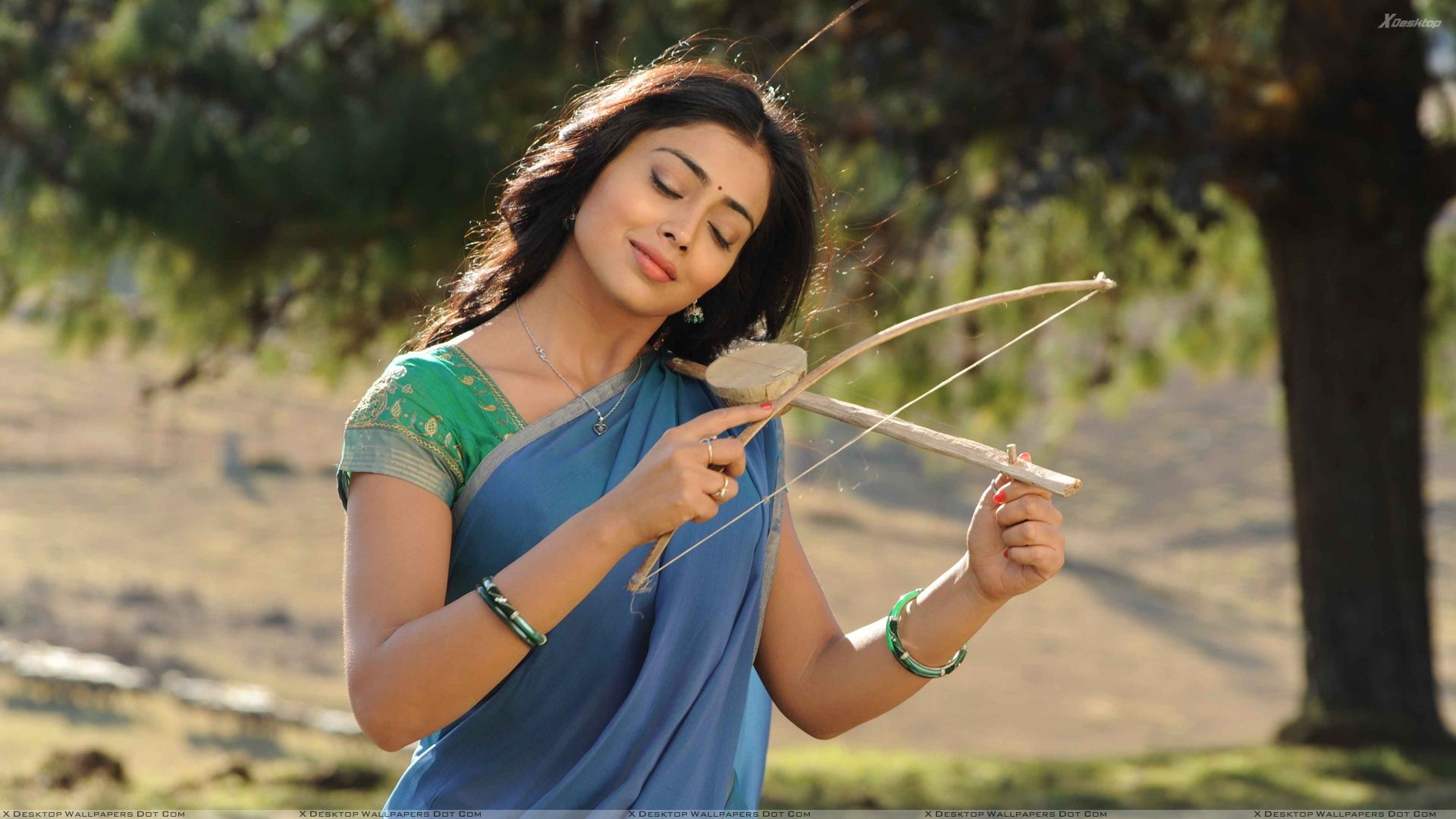 shriya saran closed eyes n instrument in hand in kutty movie wallpaper